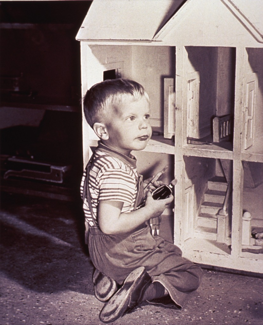 <p>A little boy playing with a large doll house.</p>