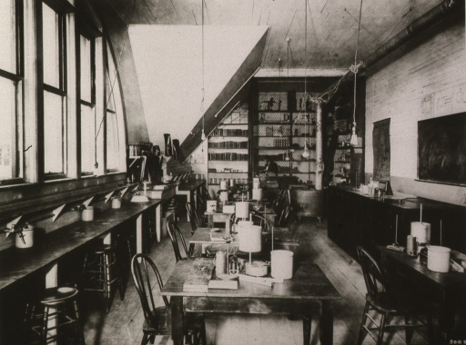 <p>Interior view of physiology laboratory ca.1912 at the University of Oregon Medical School. Bookshelves in the rear comprised the School's first library.</p>