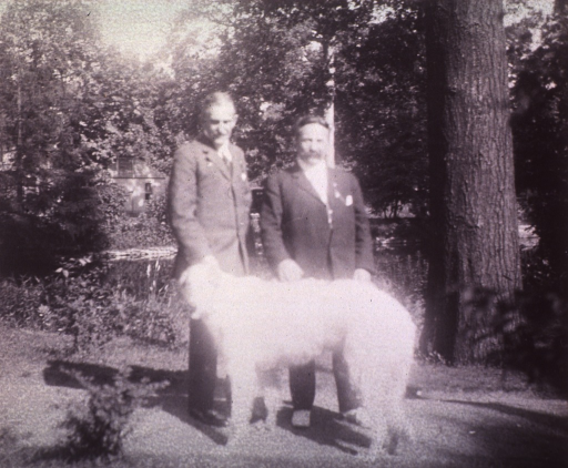<p>Full length, standing with unidentified person and a dog.</p>