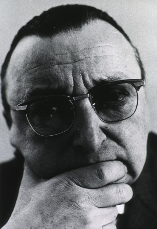 <p>Close-up, full face, hand to chin, wearing glasses.</p>