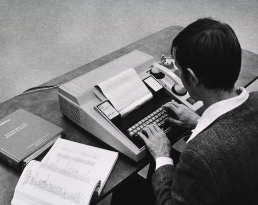 <p>Interior view: Telephone receiver is resting on the computer's modum; the Dept. of Health, Education, and Welfare's &quot;Online Services Manual&quot; is on the table with the computer.</p>