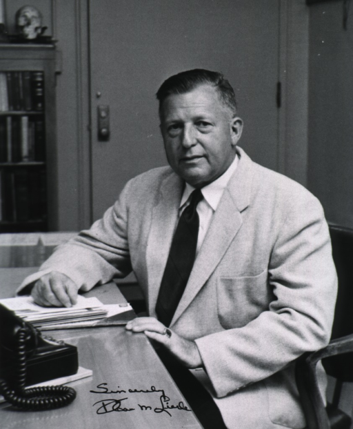 <p>Half-length, seated at desk, left pose, full face; door and bookshelves in background.</p>