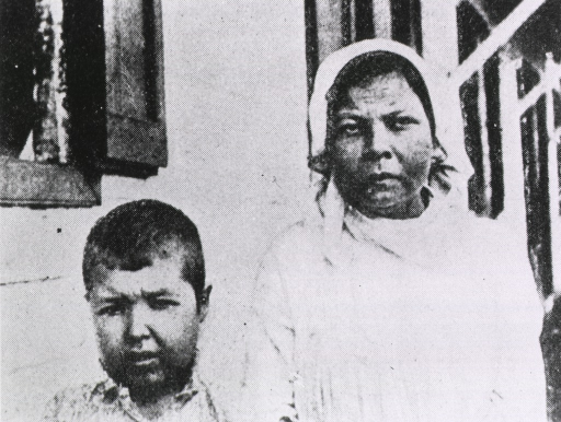 <p>Exterior view: a woman and a young boy with pained expressions on their faces.</p>