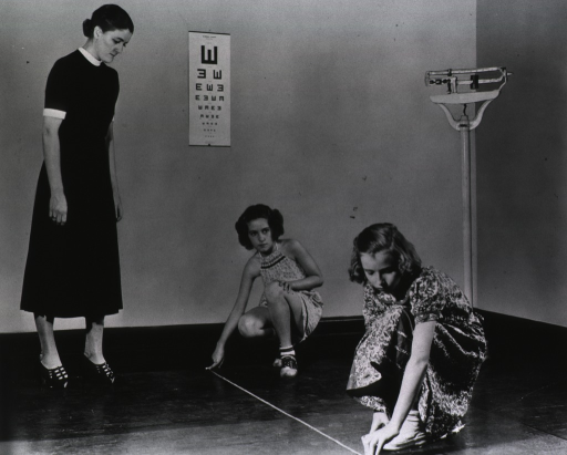 <p>Showing two female students, under the watchful eye of the teacher, determining the proper distance that one must stand from an eye examination chart on the wall.</p>