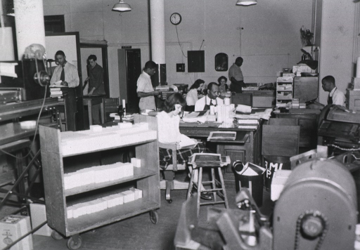 <p>Interior view: Staff members are working with cameras, microfilm readers, cutting boards, photostats, books.</p>