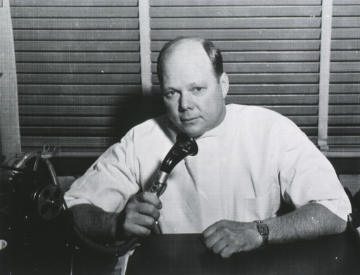 <p>Half-length, seated at desk, full face; speaking into a Dictaphone.</p>