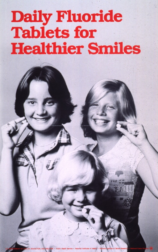 <p>Black and white poster with red lettering.  Title at top of poster.  Visual image is a reproduction of a b&amp;w photo of three children smiling and holding fluoride tablets.  Publisher information at the bottom of poster.</p>