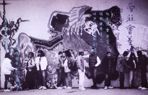 <p>Black and white poster with aqua and purple lettering.  All lettering in what appear to be Chinese characters.  Entire poster is a b&amp;w photo reproduction featuring an urban street scene.  People of varying ages and ethnicities congregate in front of a wall that bears a mural dealing with death.</p>
