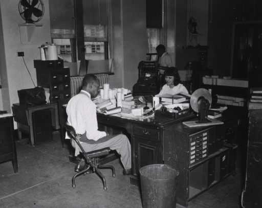 <p>Interior view:  Army Medical Library.  Reference Division.  Staff members at work stations.</p>