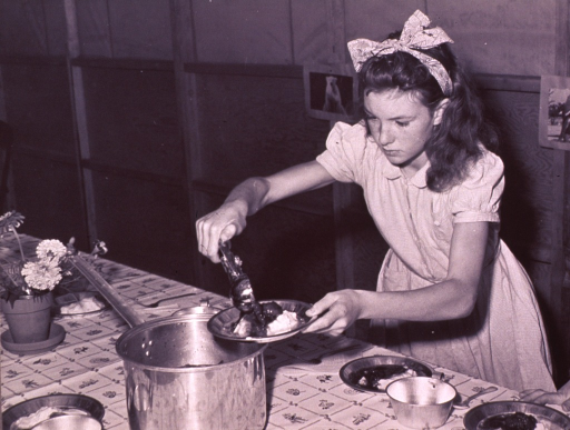 <p>A girl is scooping stew from a large pan onto mashed potato in pie tins.</p>