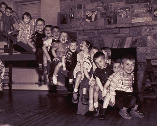 <p>Group of nursery school children on a wooden slide inside a model facility.</p>