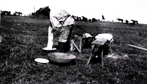 <p>A soldier washes clothes in basins in the middle of a field.  Horses are in the background.</p>