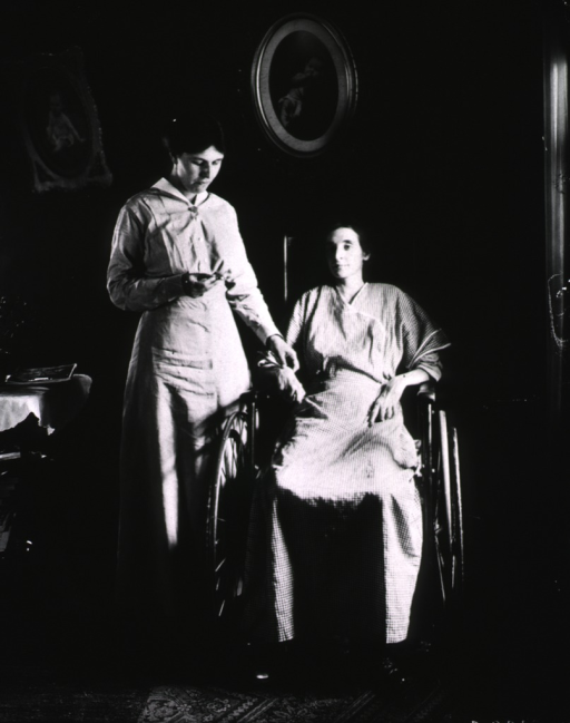 <p>View of a nurse taking the pulse of a woman in a wheelchair in the comforting surroundings of the woman's home.</p>