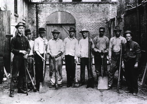 <p>Group portrait of nine rat-proofers, posed standing, holding sticks, pick axes, and shovels, during the Public Health Service campaign against the New Orleans plague epidemic, 1914-1920.</p>