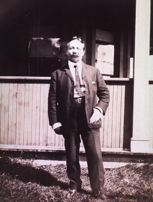 <p>Full length, standing in front of building; left hand at coat pocket.</p>