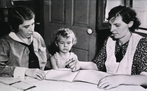 <p>Showing a mother and her daughter seated at a table with a Nutrition worker.  The mother is being instructed on how to prepare a budget.</p>