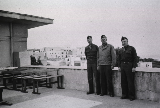 <p>Three unidentified servicemen in uniform pose on the roof terrace of the 54th Station Hospital.</p>