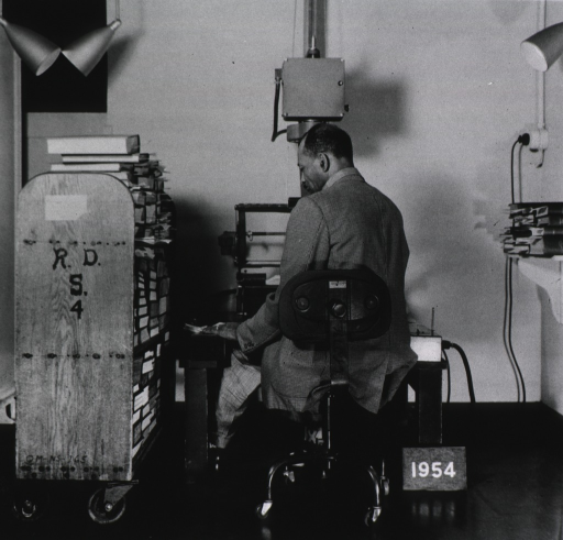 <p>Interior view:  Photoduplication Section.  Mr. Gibson seated at microfilm camera with truck of publications nearby.</p>