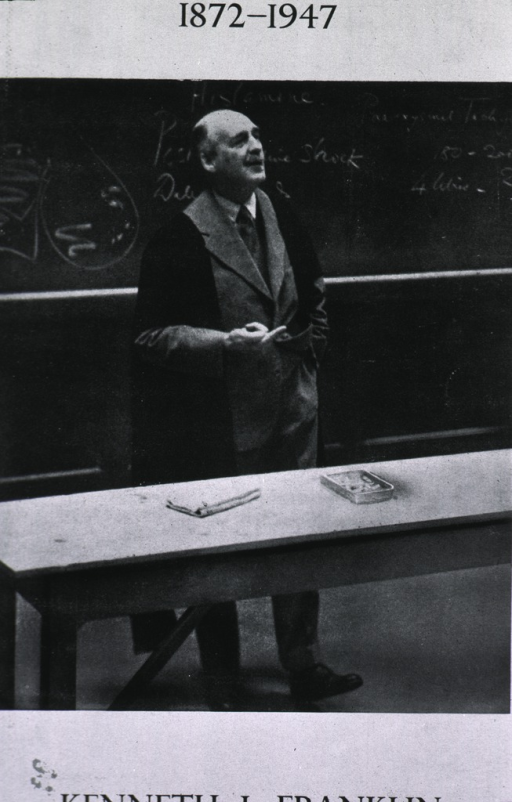 <p>Standing before blackboard, lecturing.</p>