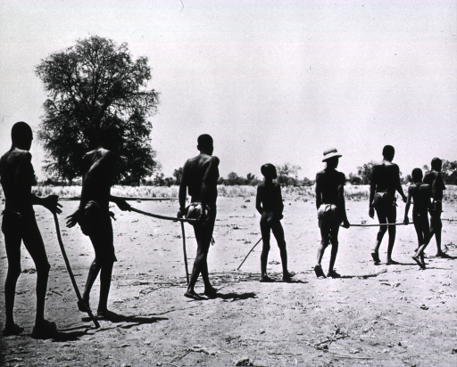 <p>Several blind adults are walking with the aid of sticks and are being guided by children.</p>