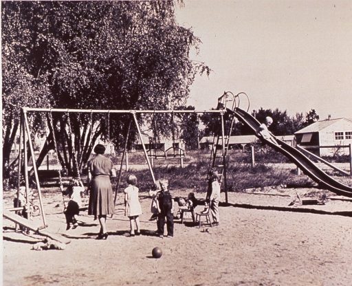<p>Children playing on swings and slide at a nursery school at an F.S.A. Farm Family Migratory Labor Camp.</p>