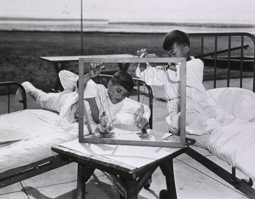 <p>Exterior view: two children, on beds placed outside in the sunshine, play with marionettes.</p>