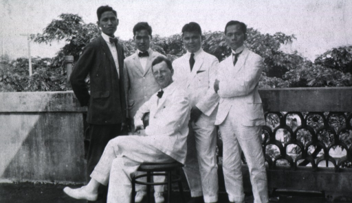 <p>Full length, seated, left pose, full face; with four unidentified persons standing behind him.</p>