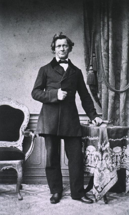 <p>Standing, arm on table, other in coat.</p>