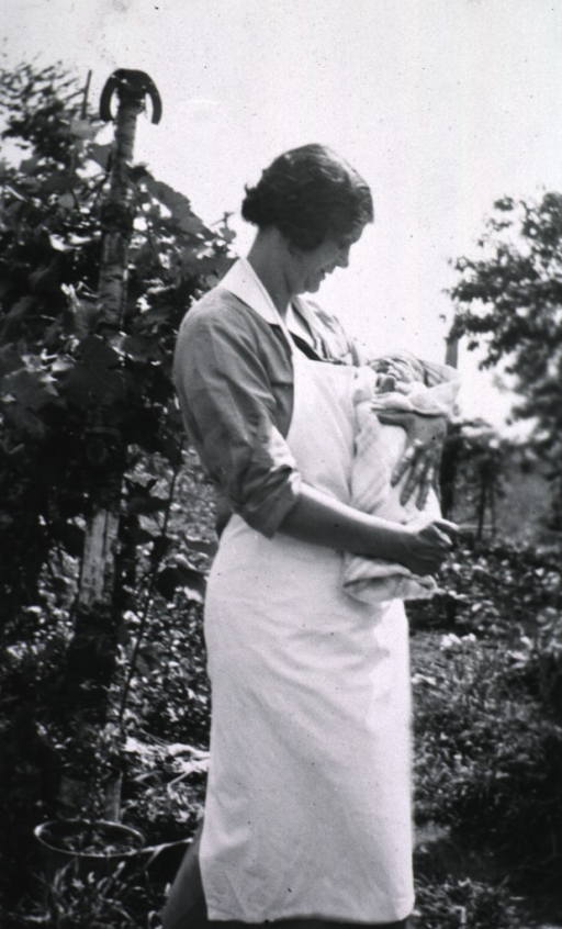 <p>Mrs. Smyth holds an infant outside.</p>