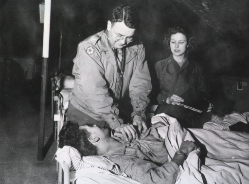 <p>A doctor leans over and unbuttons the shirt of a wounded man lying in bed while a nurse holds a medical chart and watches the patient.</p>