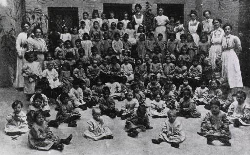 <p>Exterior view: a large group of children and several adults are gathered in the courtyard of a nursery school.</p>