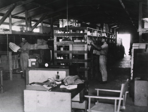 <p>Servicemen work amidst the supplies stacked on shelves in a warehouse-like room.</p>