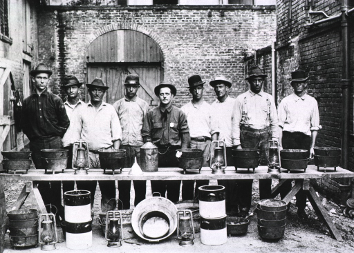 <p>Group portrait of nine men standing behind a makeshift table upon and around which are displayed kettles, buckets, lanterns, and other equipment used in catching rats during the Public Health Service campaign against the New Orleans' plague epidemic of 1914-1920.</p>