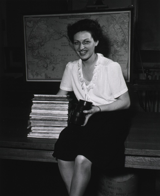 <p>Interior view:  Ruth Martin, holding rolls of film, is sitting on a table next to a stack of periodicals in the reference division photoduplication section.  A world map is in the background.</p>