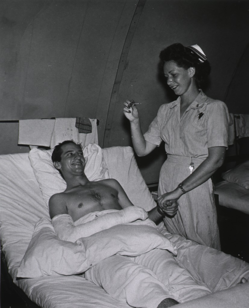 <p>Navy nurse (Lt. Bergion) taking the pulse of a patient.</p>