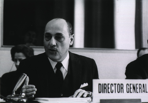 <p>Head and shoulders, full face, at meeting of Executive Board of WHO.</p>