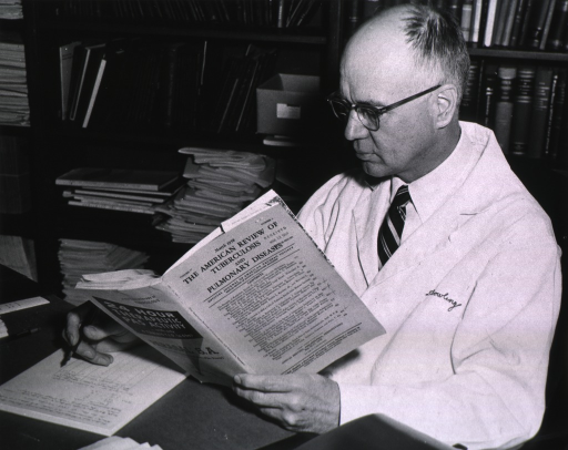 <p>Half-length, left profile, wearing lab coat, seated at a desk, reading a journal and making notes.</p>