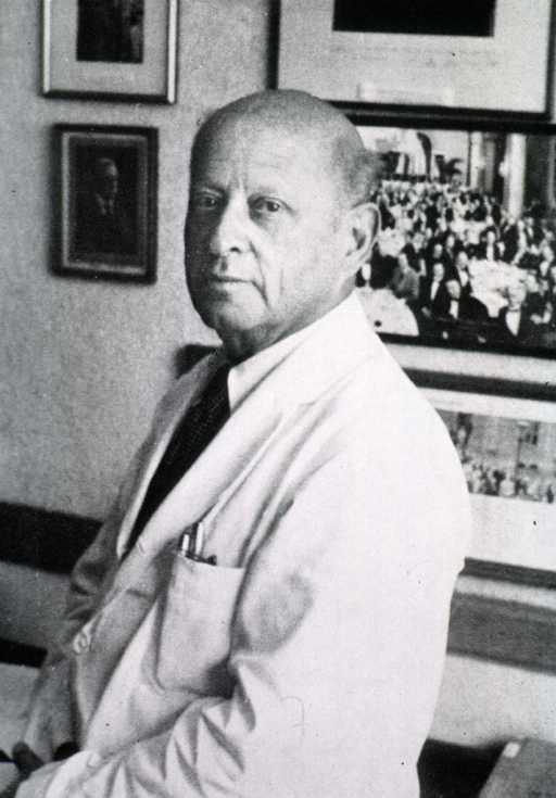 <p>Half length, full face, body to left, wearing white coat, seated on table in his office.</p>