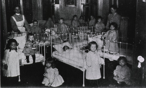 <p>Interior view: many children are sitting and standing in wrought iron cribs; a few children and two woman are standing among the cribs.</p>