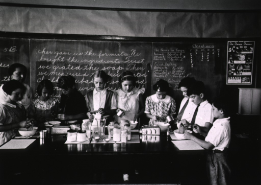 <p>In the classroom, students gathered around a large table, are going through the various stages of making tooth powder.</p>
