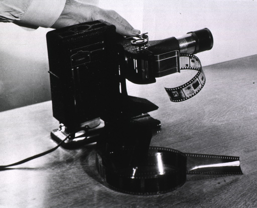 <p>Interior view: Filmstrips are in and next to the photoduplication section's Tri purpose SVE projector, model AAA, manufactured by the Society for Visual Education, Inc. in Chicago.</p>