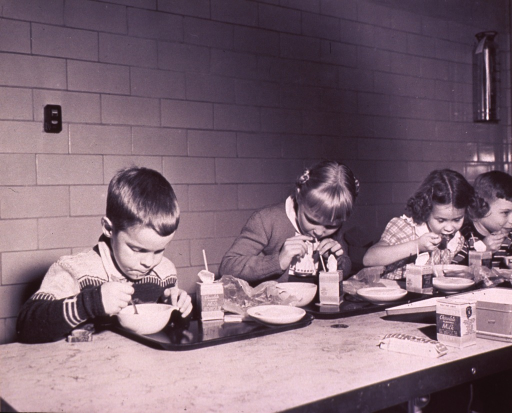 <p>Children are eating lunch in a school cafeteria.</p>