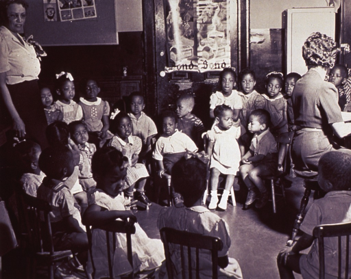<p>African American children at the Northwest Settlement House are gathered together for a song session.</p>