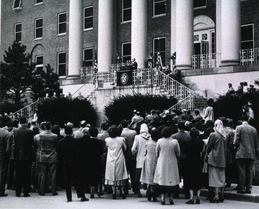 <p>View from behind audience showing front of Building 1 and speaker at podium.</p>
