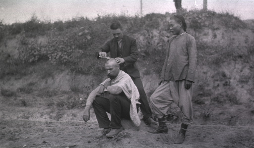 <p>A soldier gets his hair cut while sitting in a field in Gungalin.</p>