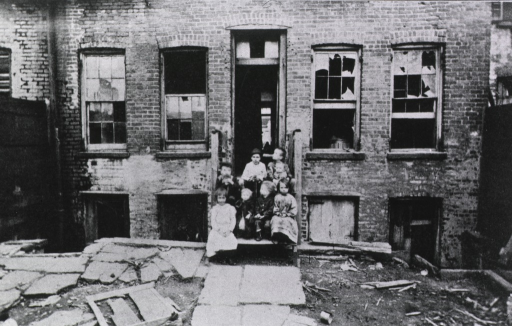 <p>Exterior view: a group of children are sitting on the steps to a building with broken windows throughout; the ground in front of the building is covered with debris. With the exception of the infant, these are all working children.</p>