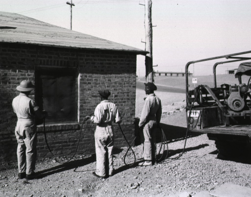 <p>Two men hold a hose that extends from the back of a truck parked next to the brick billet.  A third men directs the nozzle of the spray towards the covered window of the billet.  On the back of one of the men's work shirts is inscribed &quot;MC.&quot;</p>