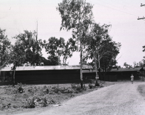 <p>Exterior view of complex of buildings next to a gravel road.  A nurse walks down the road toward the camera.</p>