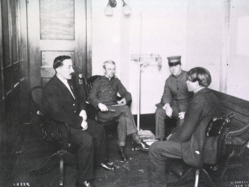<p>Four men seated in a room, two of them are in uniform (Eugene Mullan and an immigration officer); a young man and an interpreter sit in the foreground.</p>