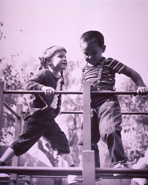 <p>Two children are climbing on playground equipment.</p>